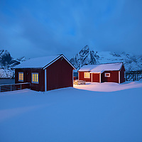 Snow covered red Rorbu cabins in winter dawn twilight at Hamnøy, Moskenesøy, Lofoten Islands, Norway