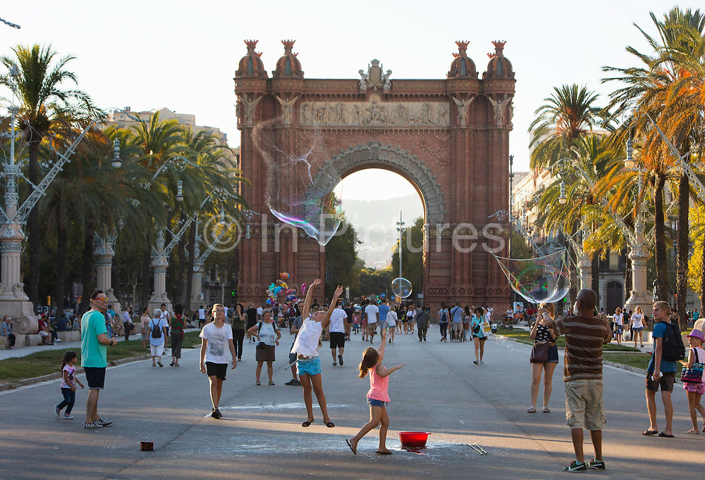 Children play with bubbles surrounded by people on their summer evening paseo walk in the Parc de la Ciutadella overlooked by the Arc de Triomf, which was originally the gateway to the 1888 Universal Exhibition, on 5th July 2016, Barcelona, Spain.