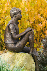 Statue 'Boy on a Rock'  by Jane Hogben in front of Cornus sanguinea 'Midwinter Fire' in autumn colour