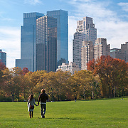 A couple walks across Sheep Meadow in Central Park, New York City in autumn