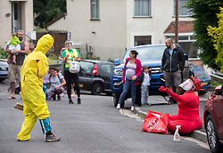"© Licensed to London News Pictures; 26/07/2020; Bristol, UK. ""Hazmat"" (in yellow) & ""Covid"" (in red) perform on the streets of St Annes in The Bristol Coddywomple with a colourful clown show created specifically for these times of the coronavirus pandemic. The comedy double act consists of the virus, Covid 19, who is naive and playful, and a bright yellow Hazmat suited character who attempts to 'control the virus'. The Bristol Coddywomple is an ambling celebration of street performance with more than 40 performance artists, entertainers and musicians taking ambling versions of their shows out into their local areas, giving them a chance to show off their talents to live audiences while venues remain shut due to the coronavirus Covid-19 pandemic and lockdown when much art and performance has been unable to take place in normal venues. This is the first one of its kind in the UK, with the Coddywomplers performers of many types performing on the streets following pre-mapped and publicised routes to entertain their neighbours as they pass through with music, circus and visual treats. Audiences can watch from their windows and doorways, or come outside to interact with the entertainers from their front yards. Photo credit: Simon Chapman/LNP."