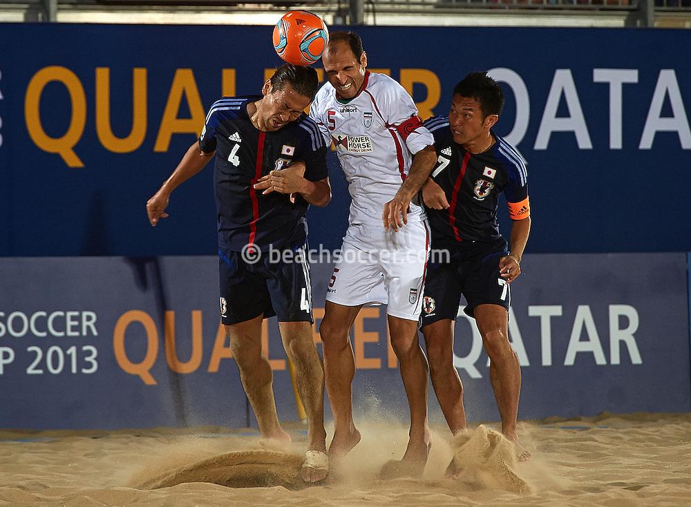 DOHA, QATAR - JANUARY 26:  Shinji Makino and Takeshi Kawaharazuka of Japan compete for the ball with Ali Naderi Hosseinabadi of Iran during the FIFA Beach Soccer World Cup 2013 Qualifier Qatar at Katara Beach on January 26, 2013 in Doha, Qatar. (Photo by Manuel Queimadelos)