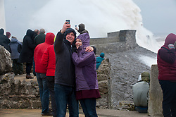 © London News Pictures. 08/02/2014. Porthcawl, UK. Members of the public gather to watch waves crash against the lighthouse in Porthcawl, Wales during a storm. Photo credit : Graham M. Lawrence/LNP.