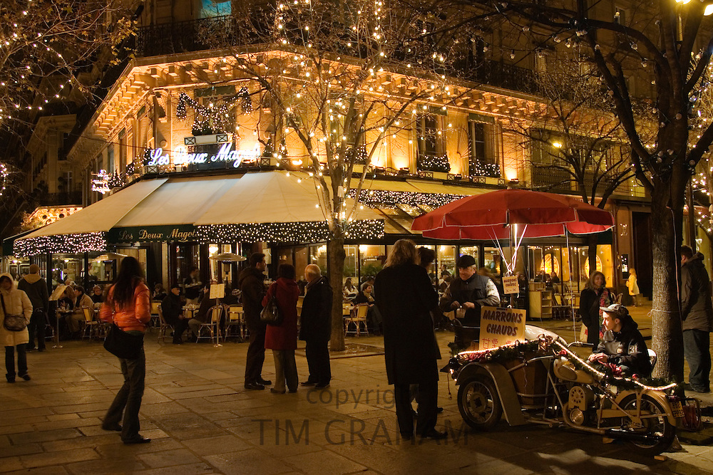 Roasted chestnut street seller outside Les Deux Magots Cafe and Restaurant, Boulevard St Germain, Paris, France