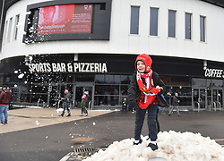 A young Bristol City's fan plays in the snow before the game.