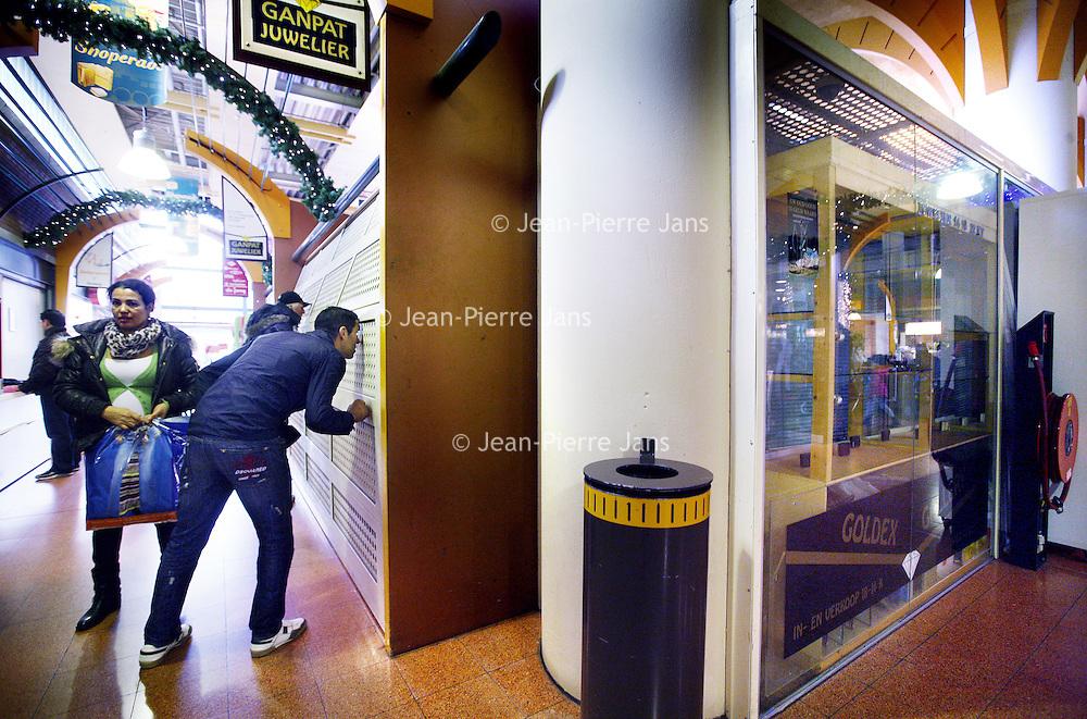 Nederland, Amsterdam , 30 november 2013.<br /> Bezoekers van de Shoperade op het Osdorpplein kijken door de kieren van de gesloten juwelier Ganpat naar de ravage daags ervoor als gevolg van een overval. Overigens voor de derde keer op een rij.<br /> <br /> Foto:Jean-Pierre Jans