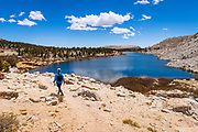 Hiker exploring the Cottonwood Lakes Basin at Lake #3, John Muir Wilderness, California USA