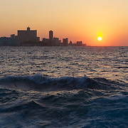 Looking out over the Malecon the sun sets over the western side of Havana, Cuba.
