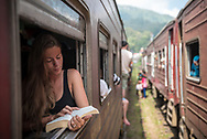 A traveler reads a book while her train, traveling to the Sri Lankan town of Ella, pauses on the tracks at another station en route. (April 9, 2017)