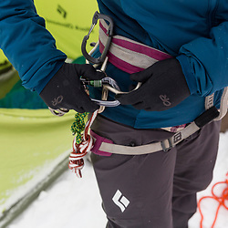 A woman organizes her climbing gear while winter camping in New Hampshire's White Mountains. Randolph Community Forest.