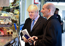 © Licensed to London News Pictures. 14/05/2013. London, UK (Left to right) Boris Johnson and Lord Adonis, Chairman of the Crossrail 2 Task Force for London First buy a coffee from a concession stall at Wimbledon Station.  The Mayor of London, Boris Johnson, leads a short walkabout around Wimbledon High Street to meet local people as he helps launch a public consultation on proposed routes for Crossrail 2. Today 14th May 2013. Photo credit : Stephen Simpson/LNP