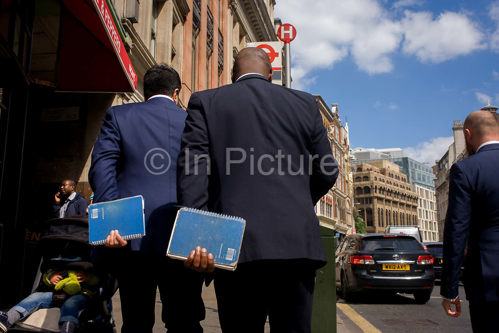 Three blue-suited businessmen walk along a City of London street holding identical blue spiral-bound notebooks. The three gentlemen are possibly en-route to a nearby city meeting, using the same stationery issued by the boss or from the office supplies cupboard. The moment is faintly comical as the men wear almost identical suits with similar shades of blue, popular among young city workers in 2015.