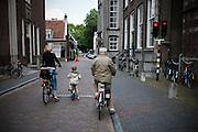 Fietsers wachten keurig voor het rode verkeerslicht.<br /> <br /> Three generations of cyclists are waiting at a traffic light