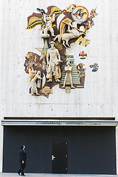 Man walking in front of high relief mosaic sculpture by Millard Sheets on entrance to the Mercantile Continental Building, Dallas, Texas, USA.   The 30 foot high mosaic of cowboys, indians, native Americans,  horses and wild animals stands 30 feet high.