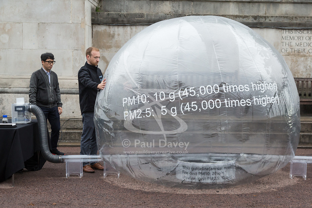 Dr Michael Whitely, Head of Fuel Cell Engineering at UCL steadies a balloon containing dirty air - pollution particulates  as Hyundai UK demonstrates the Hydrogen-powered Nexo that not only produces completely clean emissions but also cleans up the air its engine ingests, thanks to a filtration system developed by scientists at University College London. UCL London, October 17 2018.