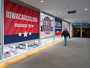 31 JANUARY 2020 - DES MOINES, IOWA: People walk past decals put in the windows of the Des Moines Skywalk welcoming people to the Iowa caucuses. Downtown Des Moines is preparing the caucuses, which are Monday, February 3. The city has hung banners throughout the city center and put signs in the skywalk. Some candidates are also buying advertising in the skywalk.   PHOTO BY JACK KURTZ