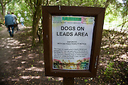 A sign in alongside a foot path warning that dogs should be kept on a lead or owners risk paying an 80 GBP penalty. Leybourne Lakes Country Park. Snodland, Kent, UK Sunday August 10th 2014