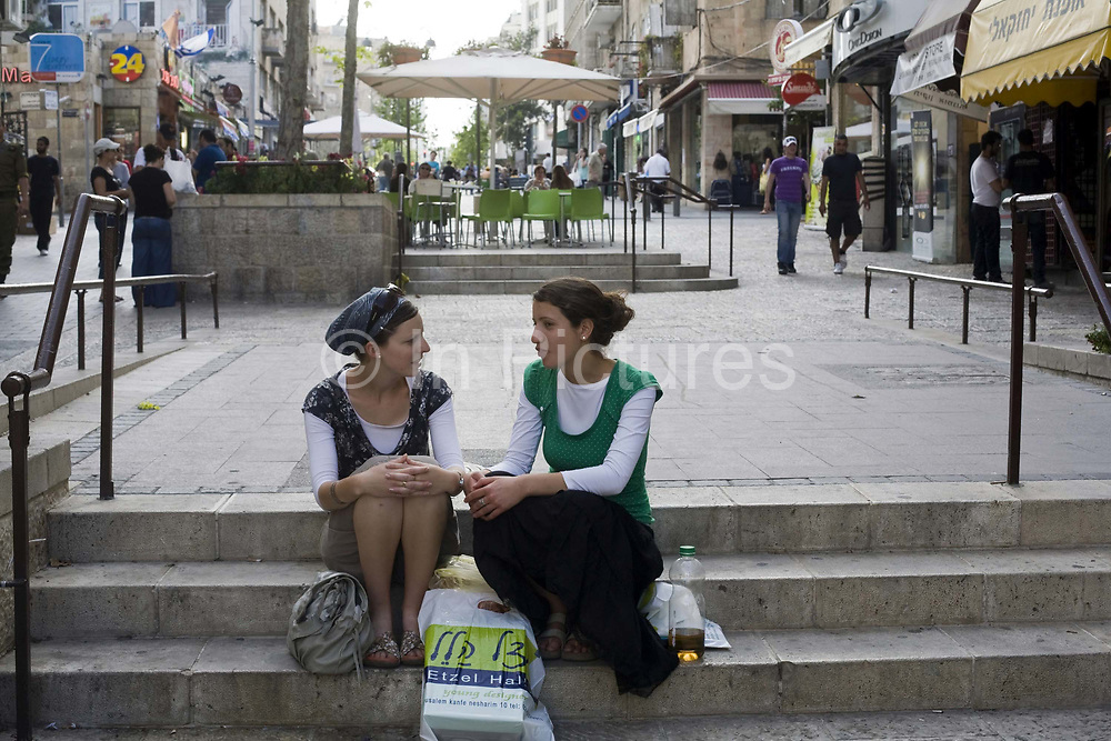 Two girls sit and talk on some steps in Ben Yahuda Street, Jerusalem, Israel