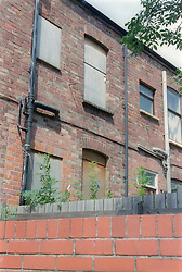 Brick building with boarded up windows,