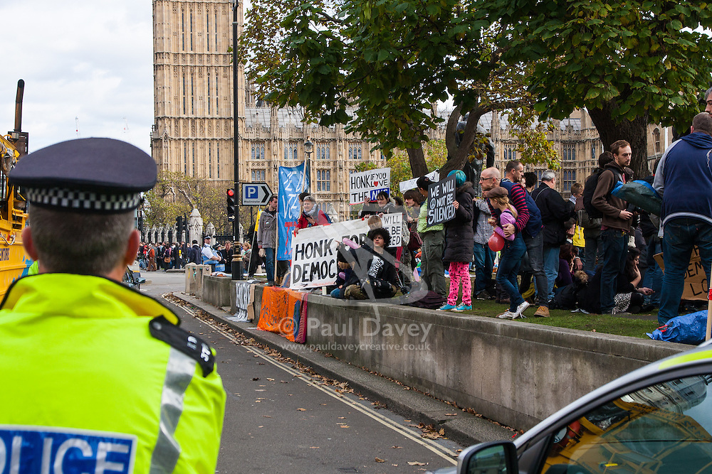 """Parliament Square, London, October 25th 2014. Activists from Occupy Democracy continue their small protest against """"capitalism's usurping of democracy"""", outside Parliament. They demand that the government puts """"people before profit"""" and that the proposed TTIP protocol between Europe and the US is dropped, and that attempts to further privatise the NHS and other public services are stopped. Heritage Wardens from the GLC continue with the support of dozens of police officers to keep the protesters on the periphery of parliament square, occasionally taking banners and posters from the protesters. PICTURED: Police officers watch as protesters ask passing traffic to """"honk for democracy""""."""