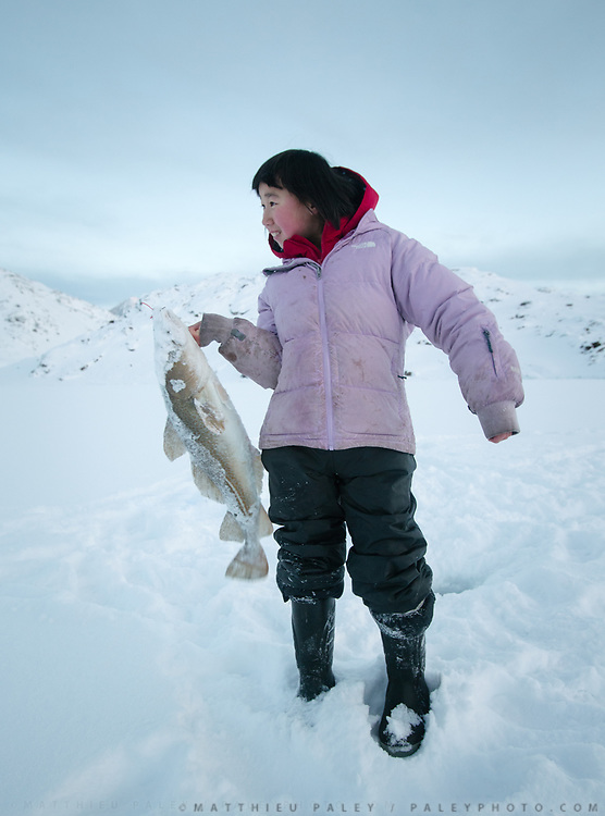 Sunday family fishing trip (arctic cod) in ice holes, with hunter Tobias Ignatiussen, his wife Silba, daughter Gerda and two friends Naima and Laila.<br /> Life in and around the Inuit settlement of Tasiilaq (population of 2000), in East Greenland.