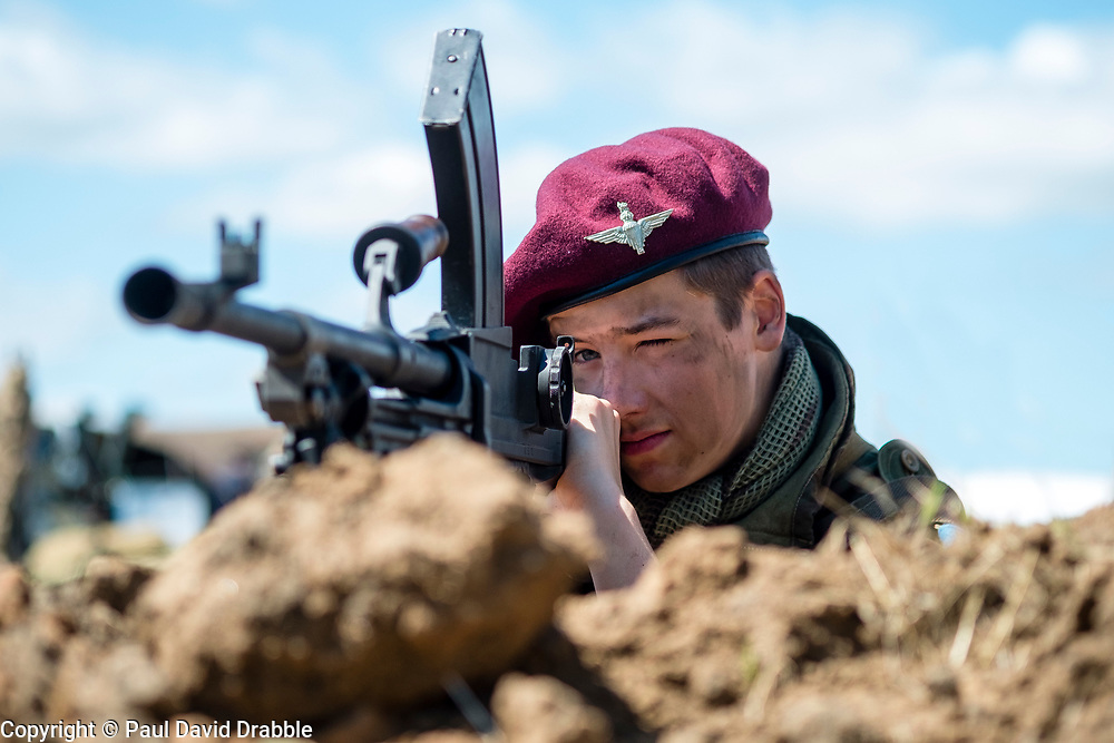 A reenactor portrays a British Paratrooper of the 12th (Yorkshire) Parachute Battalion, 6th Airborne Division, wearing the Icon maroon beret and using a Bren light machinegun.