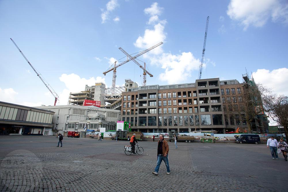 Mensen lopen over Vredenburg waar een nieuw woonblok is verrezen.<br /> <br /> People walking at Vredenburg with in the background the construction area of the new buildings.