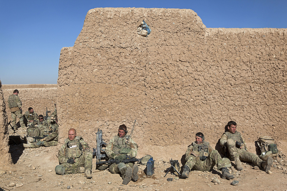 A group of British soldiers of 16 Air Assault Bde's elite BRF (Brigade Reconnaissance Force) take a break after searching a compound for weapons and explosives during a dawn raid as part of an operation in the Western Dasht, Helmand Province, Southern Afghanistan on the 20th of March 2011.