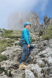 Teenage boy climbing steep rock face
