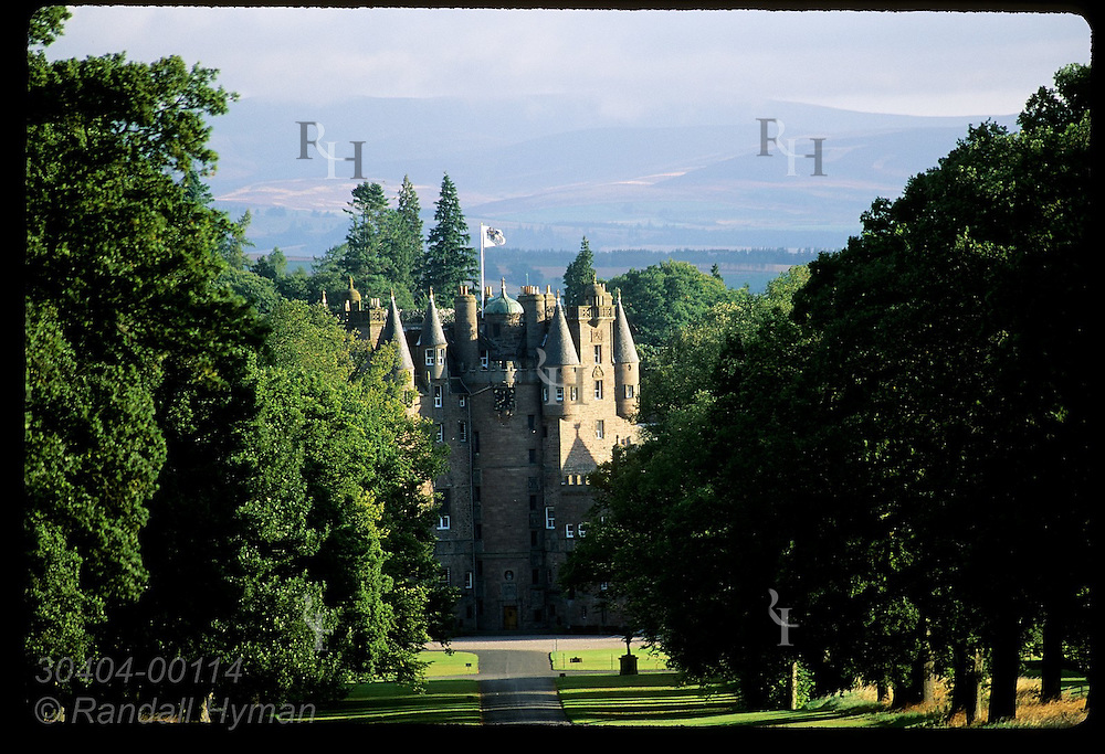 Tree-lined avenue leads to Glamis Castle, childhood home of Queen Mother; town of Glamis, Angus, Scotland.