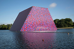 © Licensed to London News Pictures. 18/06/2018. London, UK. Swimmers pass close to artist Christo's latest work 'The Mastaba' unveiled on The Serpentine in Hyde Park today. The 20m high installation, made up of 7,506 horizontally stacked barrels, is 30m wide and 40m long. Photo credit: Peter Macdiarmid/LNP