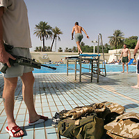 Baghdad, Iraq, 2 Oct 2005. Running 'Route Irish'...Troops at the 'Liberty Pool'...B Company, 1st Battalion, The Royal Irish Regiment, a tight-knit multi national fighting force make daily escorting runs along ?Route Irish?, the infamous Baghdad Airport road. The 46 man team are all British Army regulars but come from as far afield as Fiji, South Africa and Northern and Southern Ireland. Previous deployments in Kosovo, Sierra Leone and Northern Ireland have equipped them with the valuable skills needed to provide protection for British Forces and materials transiting the world?s most dangerous highway. Due to an increased presence of US forces along the route both in dug in positions and mobile patrols, attacks along the road have slackened, despite this a day rarely passed without an IED (improvised explosive device) being detonated or a small arms attack against coalition forces. ..The convoy attempts to maintain a seclusion ?bubble? around its vehicles for the duration of the journey. Any civilian vehicle that either strays into the bubble or refuses to keep their distance represents a threat and should they ignore the warning blasts on air horns carried in each vehicle the rules of engagement progress from warning shots to use of lethal force. The relative safety of the International Zone offers them an opportunity to decompress between missions. A duty driver ferries soldiers to the ?Liberty Pool?. Once only frequented by Iraq?s Ba?athist elite the luxury swimming pool and gym now fills with troops. Their body armour, helmets and weapons all within easy reach they either soak up the sun or compete with each other in diving competitions. After a daily briefing the troops have access to the ?Mosquito and Camel? bar where they watch TV or play pool and in accordance with the ?2 can rule? are allowed to drink 2 beers per night.