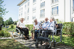 Senior man and women spending time together at garden, Bavaria, Germany, Europe
