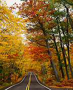 US 41 passing through canopy of northern hardwood forest at the peak of autumn color, Keweenaw Peninsula southwest of Copper Harbor, Upper Peninsula of Michigan.