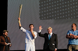 © Licensed to London News Pictures. 26/07/2012. London, UK.     The Olympic Torch Relay finale concert at Hyde Park.  The final Olympic Torch Bearer, Tyler Rix, comes onstage to meet the Mayor of London Boris Johnson, and light the Olympic Flame.   Photo credit : Richard Isaac/LNP