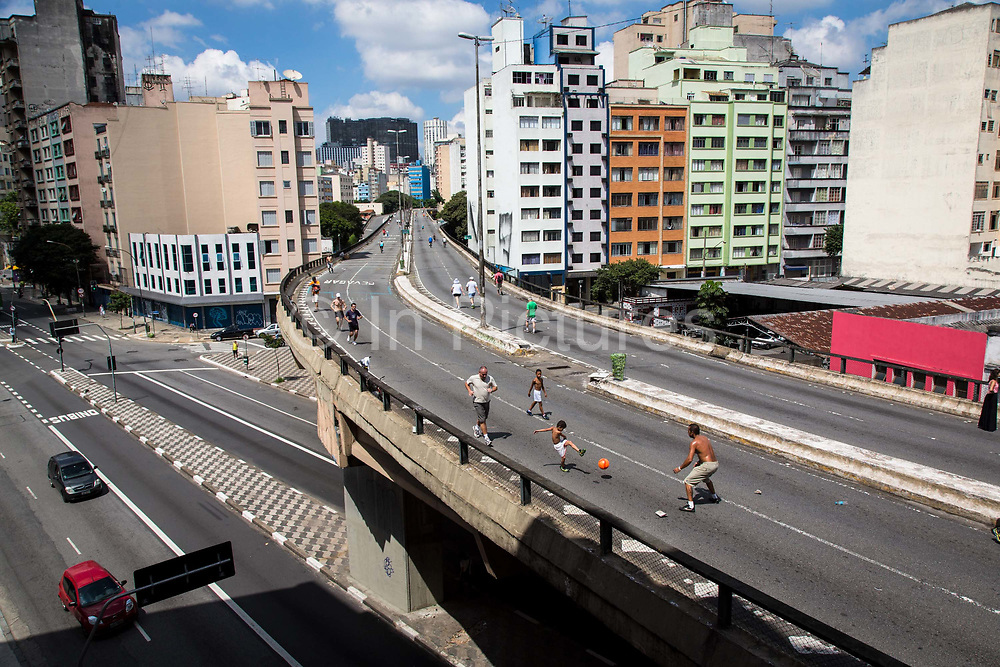 """On a Sunday a major through road running through the heart of the city centre of Sao Paulo, the """"Minhocao"""" serves as a improvised football pitch and jogging and cycling surface for city dwellers."""