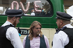 London, UK. 31st August, 2021. Metropolitan Police officers arrest an environmental activist from Extinction Rebellion after a vintage bus was used as base to block a road junction to the south of London Bridge on the ninth day of Impossible Rebellion protests. Extinction Rebellion are calling on the UK government to cease all new fossil fuel investment with immediate effect.