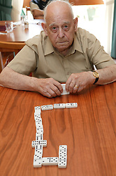 Elderly man sitting playing dominos,
