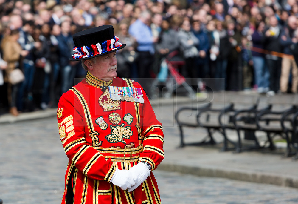 © Licensed to London News Pictures. 21/04/2016. London, UK. A Beefeater watches the Honourable Artillery Company (HAC) fire a 62 round gun salute at The Tower of London, near Tower Bridge to mark the 90th birthday of Great Britain's Queen Elizabeth II. A Royal Salute normally comprises 21 guns, but is increased to 41 if fired from a Royal Park or Residence and uniquely, at The Tower of London, a total of 62rounds are fired on Royal anniversaries, including an additional 21 guns for the citizens of the City of London to show loyalty to the Monarch.  Photo credit : Vickie Flores/LNP