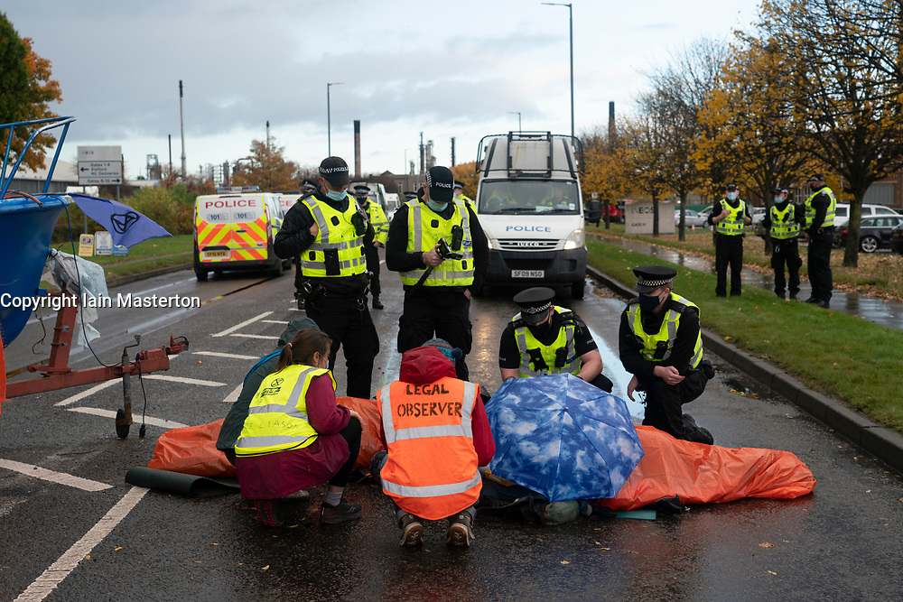 Grangemouth, Scotland, UK. 23 October 2020. Extinction Rebellion climate change protesters block entrance to INEOS headquarters at Grangemouth. Protesters have locked themselves together with chain and have parked a yacht in the road blocking access. Police have closed Inchyra Road. Pictured; Protesters are formally arrested.  Iain Masterton/Alamy Live News
