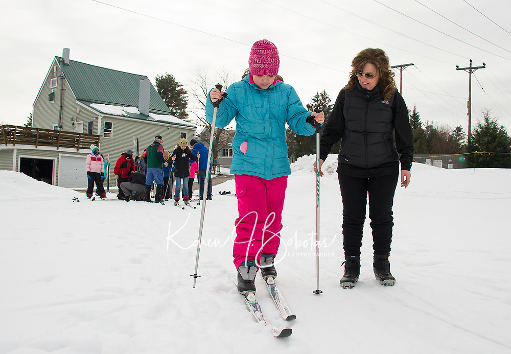 Paxten Perley gets some last minute coaching from Andrea Morin as she sets out on her cross country skis Thursday morning at Bolduc Park.  Elm Street School's fifth graders were able to experience the three Olympic sports of snowshoeing, ice skating and cross country skiing.  (Karen Bobotas/for the Laconia Daily Sun)