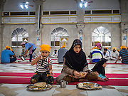 """08 FEBRUARY 2015  BANGKOK, THAILAND:  A Muslim woman and her children finish their breakfast during the community meal at the Sikh temple in Bangkok. Thailand has a small but influential Sikh community. Sikhs started coming to Thailand, then Siam, in the 1890s. There are now several thousand Thai-Indian Sikh families. The Sikh temple in Bangkok, Gurdwara Siri Guru Singh Sabha, was established in 1913. The current building, adjacent to the original Gurdwara (""""Gateway to the Guru""""), was built in 1979. The Sikh community serves a daily free vegetarian meal at the Gurdwara that is available to people of any faith and background.   PHOTO BY JACK KURTZ"""