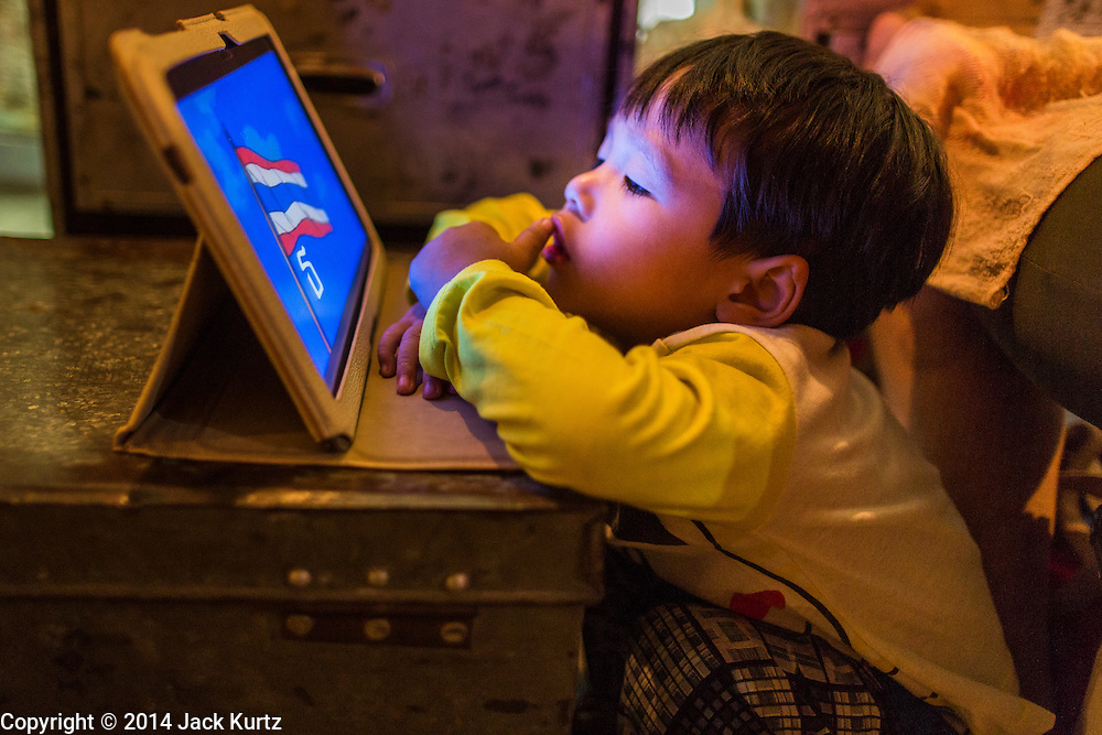 """25 JANUARY 2014 - BANG LUANG, NAKHON PATHOM, THAILAND: A child whose parents are opera performers plays with a tablet computer while his parents are on stage at a show in a Chinese shrine in the town of Bang Luang, Nakhon Pathom, Thailand. The Sing Tong Teochew opera troupe has been together for 60 years and travels through central Thailand and Bangkok performing for mostly ethnic Chinese audiences. Chinese opera was once very popular in Thailand, where it is called """"Ngiew."""" It is usually performed in the Teochew language. Millions of Chinese emigrated to Thailand (then Siam) in the 18th and 19th centuries and brought their cultural practices with them. Recently the popularity of ngiew has faded as people turn to performances of opera on DVD or movies. There are still as many 30 Chinese opera troupes left in Bangkok and its environs. They are especially busy during Chinese New Year when travel from Chinese temple to Chinese temple performing on stages they put up in streets near the temple, sometimes sleeping on hammocks they sling under their stage.     PHOTO BY JACK KURTZ"""