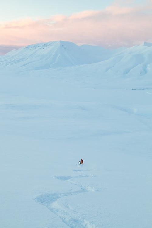Mylène Jacquemart skis down Hallwylfjellet, Svalbard at sunset.