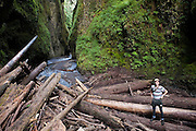 Hamilton Boyce stands on the log jam at the entrance to Oneonta Gorge, a mossy slot canyon cut into the bedrock in Oregon's Columbia River Gorge National Scenic Area.
