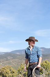 cowboy holding a lasso outdoors by a mountain range
