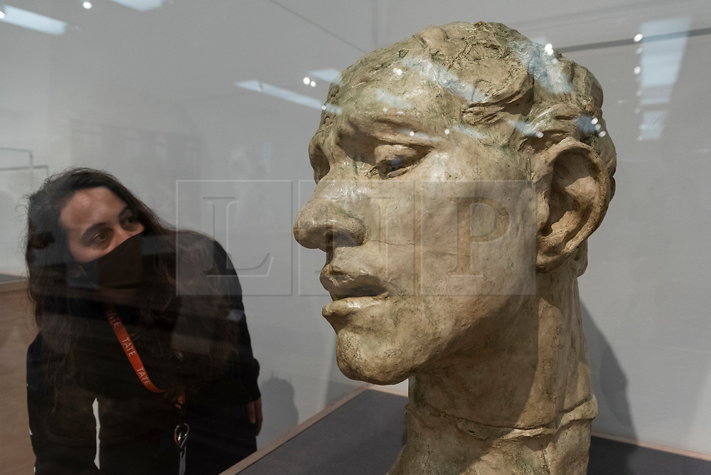 """© Licensed to London News Pictures. 11/05/2021. LONDON, UK. A staff member poses with """"Pierre de Wissant, Colossal Head"""", 1908, by Auguste Rodin. Preview at Tate Modern of """"The Making of Rodin"""", a major new exhibition of over 200 sculpture works by Auguste Rodin, many of which have never been shown outside France. The exhibition marks the reopening of the museum as the UK government eases certain coronavirus lockdown restrictions and is open 18 May to 21 November.  Photo credit: Stephen Chung/LNP"""