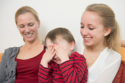 Mother with her daughter while son covering eyes, smiling