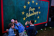 Pop Ideology sign in Shangri-La, the after-hours epicentre of the Glastonbury Festival 2013. The theme for 2013 is Afterlife with the visiters choice between heavan and hell. Glastonbury is the world's biggest greenfield festival with nearly 200,000  visiters camping in the dairy farm of Michael Evis in Somerset, UK.<br /> The first festival was in 1970 and was influenced by hippie ethics and the free festival movement. The festival retains vestiges of this tradition such as the Green Fields area which includes the Green Futures and Healing Field.