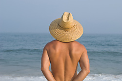 Back of man wearing a straw hat looking out at the ocean